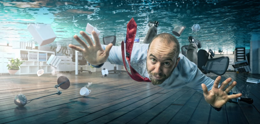 A businessman swimming in a flooded office, depicting a hurricane preparedness concept