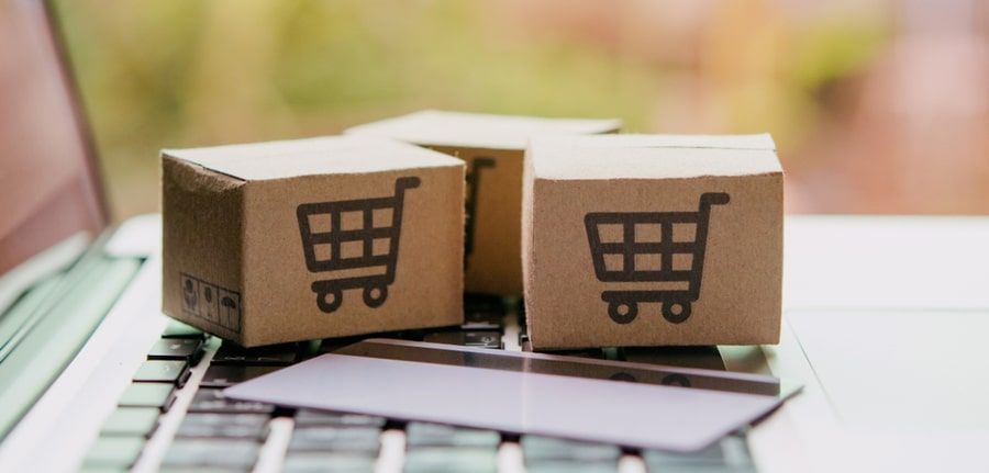 Online shopping concept depicting paper cartons or parcels with a shopping cart logo and credit card on a laptop keyboard