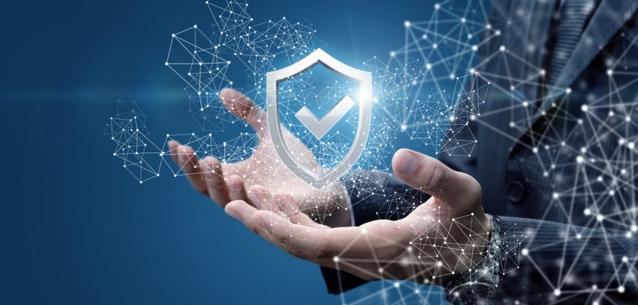 Businessman's hands below a hovering security shield with a check mark on a blue background, depicting critical cybersecurity protections