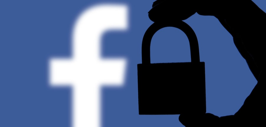 Silhouette of a hand holding a padlock infront of the facebook logo depicting Facebook security issues