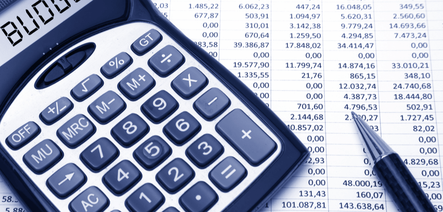 Calculator with Budget on its screen atop a worksheet filled with numbers and a pen, depicting a budget concept